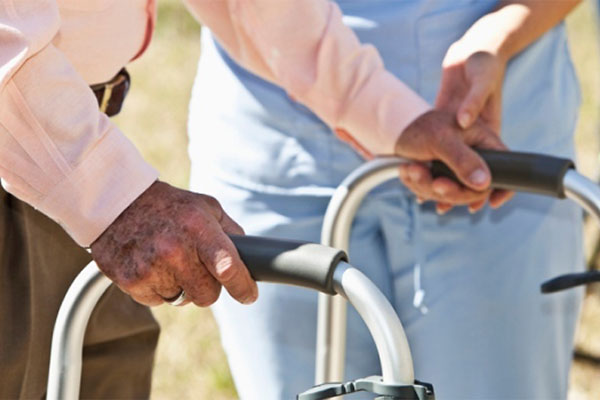 A Nurse Helping The Old Man To Walk Using  His Walker - Home Care Packages - ESP Healthcare