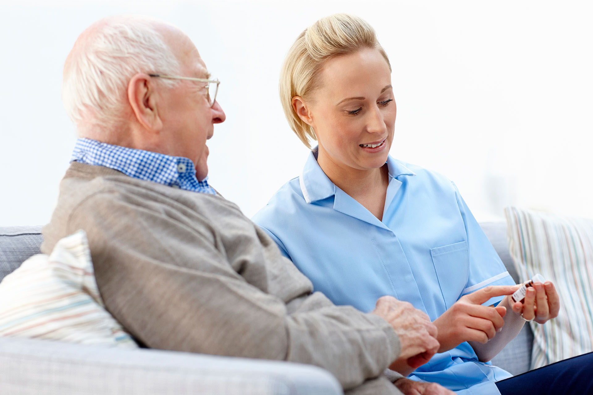 Female Caregiver Explaining To The Elderly Man His Medication - Home Care Packages - ESP Healthcare