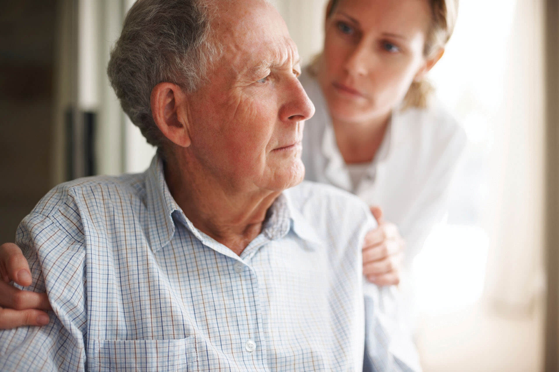 A Female Nurse Comforting An Old Worried Man - Home Care For Elderly - ESP Healthcare