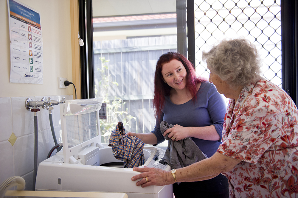 A Woman Helps An Old Woman Put Clothes In The Washing Machine - Home Care Solutions - ESP Healthcare