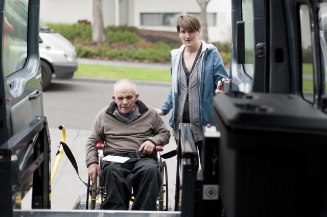 A Man Helps An Old Man In A Wheelchair In The Car - In Home Help For The Elderly - ESP Healthcare