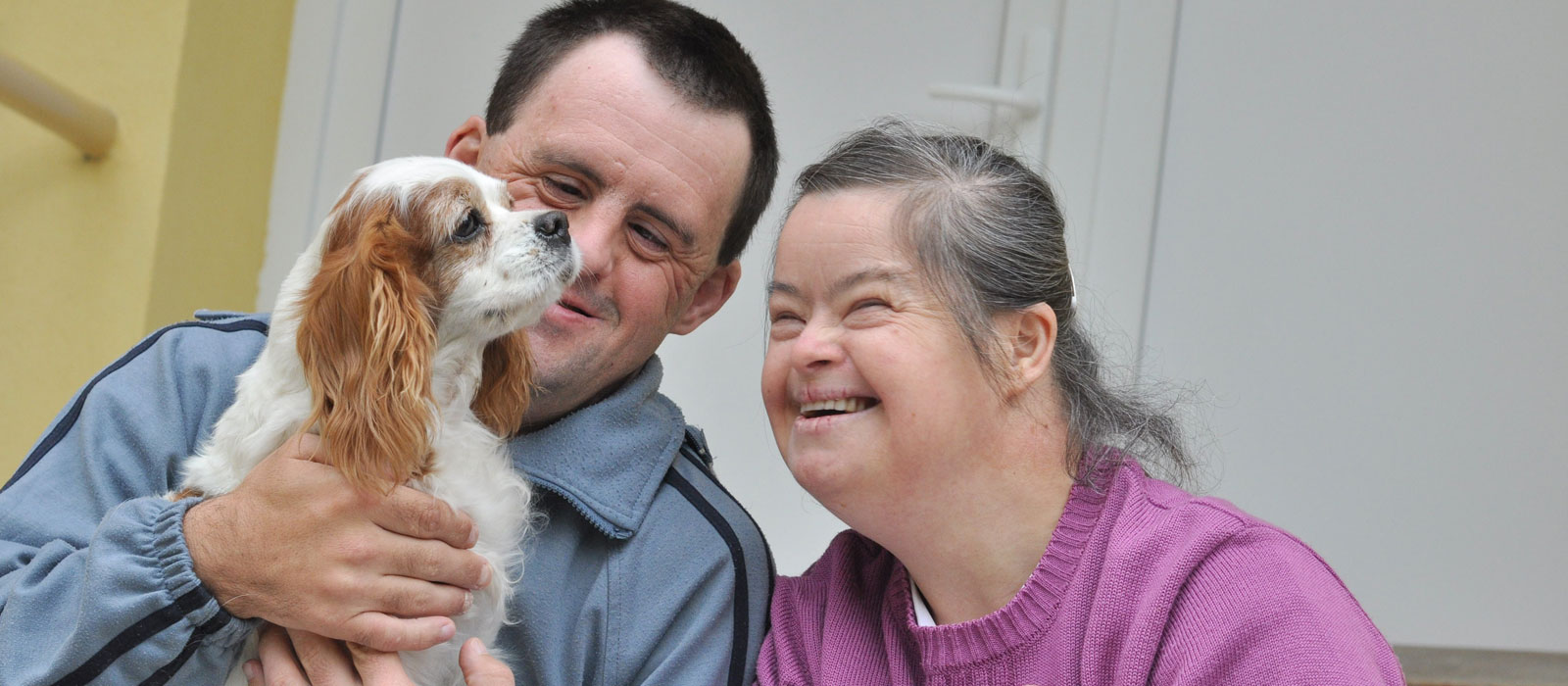 A Woman And A Man With A Down Sydrome Playing With The Puppy - Home Care Sydney - ESP Healthcare